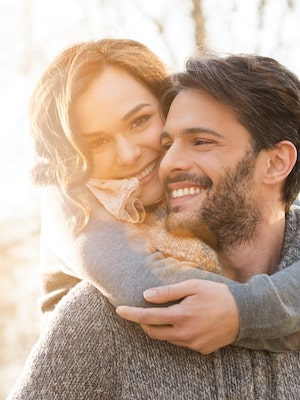 A young couple hugging outside and smiling after enjoying cosmetic dentistry