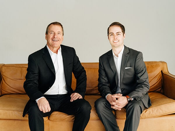 Dr. Ryan Schmidgall and Dr. Richard McDonald sitting on an orange sofa while smiling