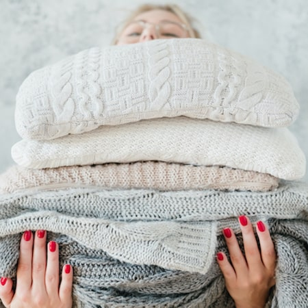 A woman holding lots of big blankets