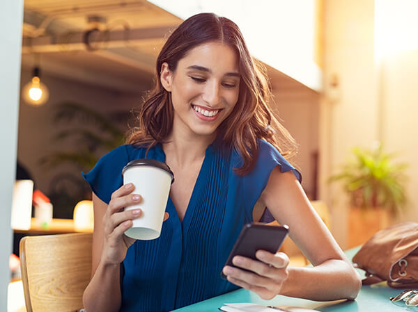 A young woman dressed in blue sitting while smiling and drinks coffee and looks at her cell phone
