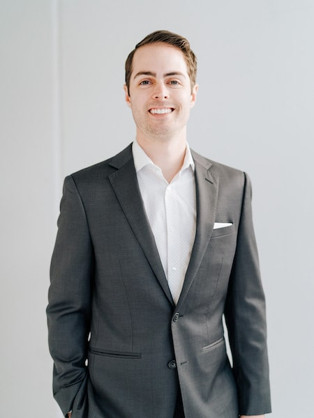 Dr. Ryan Schmidgall standing in front of a white wall wearing a black suit and white shirt