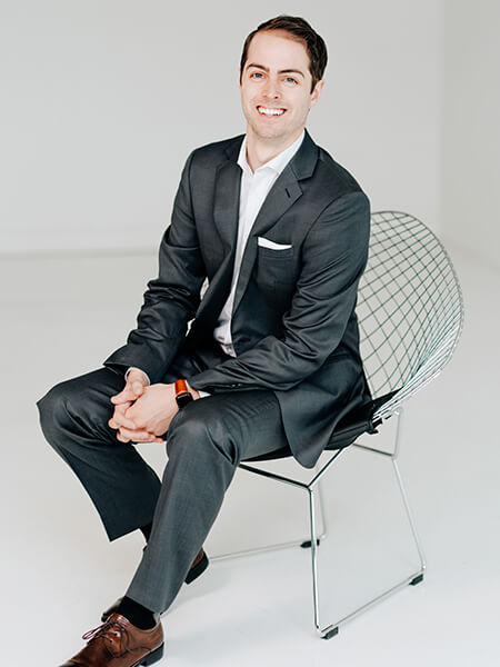 Dr. Ryan Schmidgall sitting in a chair while smiling and wearing a black suit