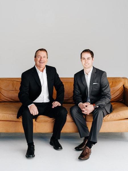 Dr. Ryan Schmidgall and Dr. Richard McDonald sitting on a tan sofa