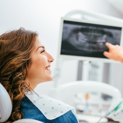 Woman sitting in a dental room looking sideways as she experiences family dentistry
