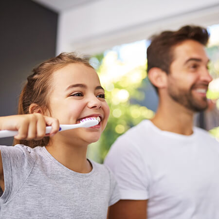 A little blond girl brushing her teeth next to her dad