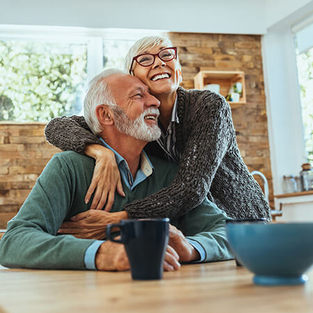 An elderly couple hugging in the kitchen while smiling