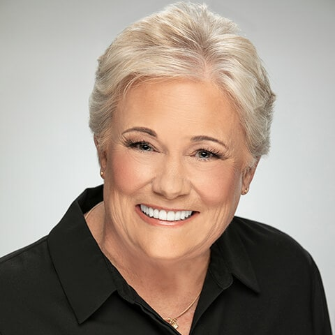 A mature white-haired woman smiling while wearing a black shirt