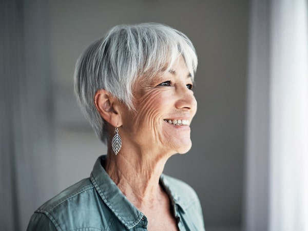 Older woman with short grey hair showing her big smile after our dental services