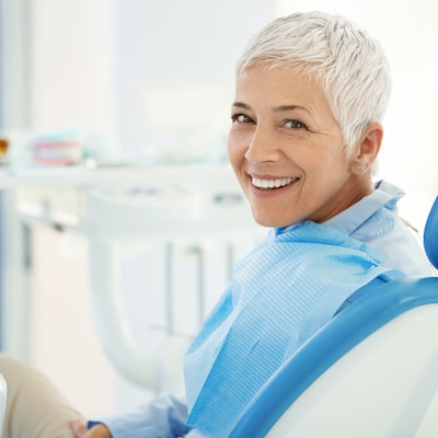 An mature woman sitting on a dental chair looking over her shoulder