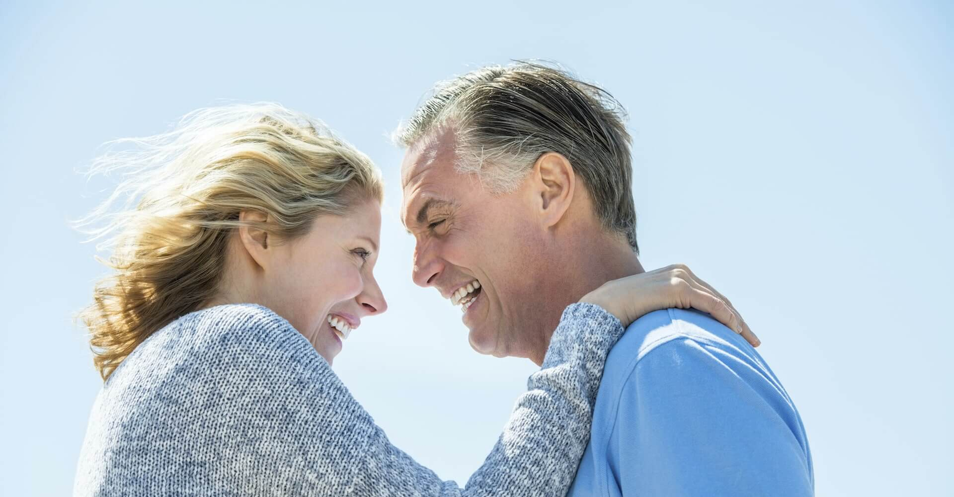 A blonde mature woman while hugging an older man