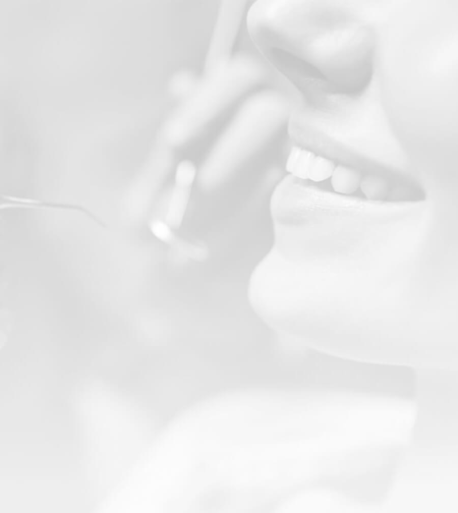A greyscale image of a smiling patient and dentist exam