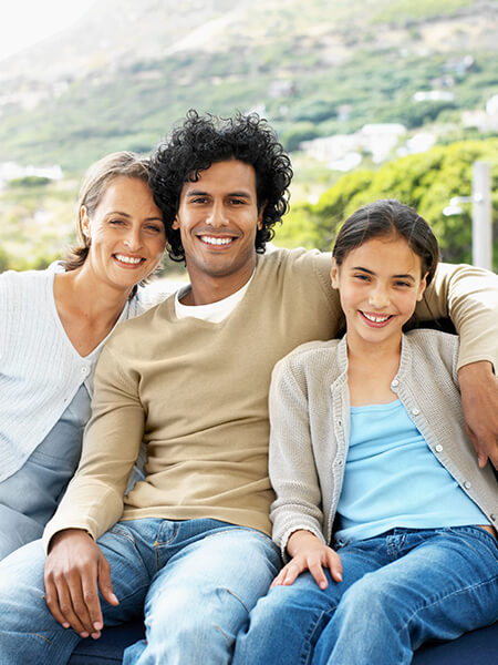 A family of three sitting on a sofa while smiling