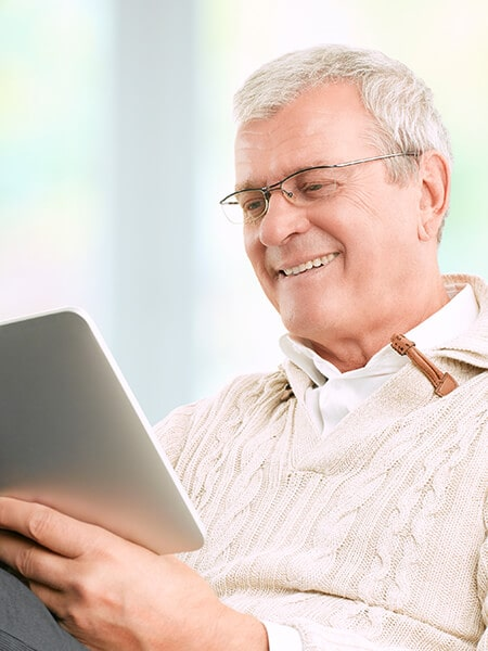 A mature man looking at his tablet while smiling