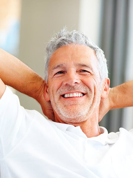 Man in white top smiling with his hands behind his head after his restorative dentistry procedure