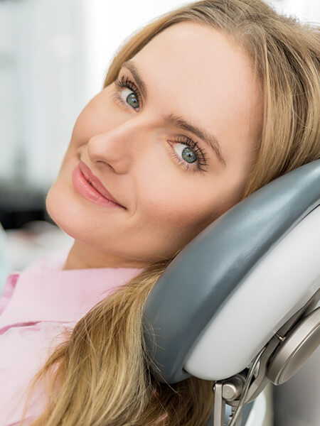 A woman at the dentist smiling while waiting for her surgery