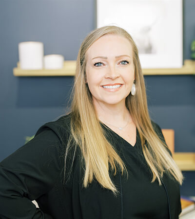 One of our dental assistants Jennifer, Ella smiles as she wears a black sweater with a gray shirt. She is blonde with long hair