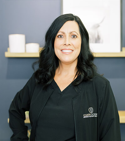 Our dental hygienist Marti, Ella smiles while wearing a black suit and two gold earrings. She has black hair