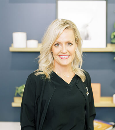 Our dental hygienist Stacy, Ella smiles as she wears a black suit with a necklace. She is blonde and has short hair